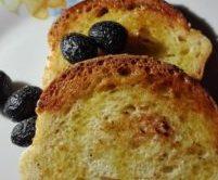 Geröstetes Brot mit Olivenöl betreufelt und in Salz konservierte Oliven